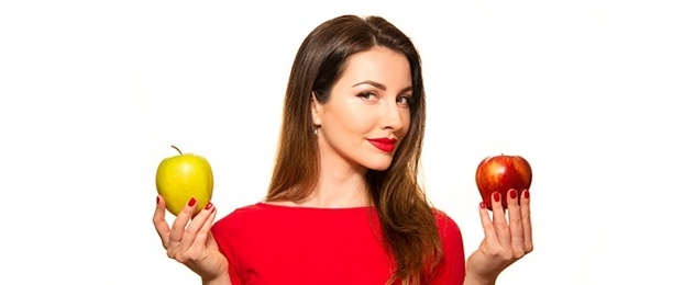 woman holding a yellow and a red apple